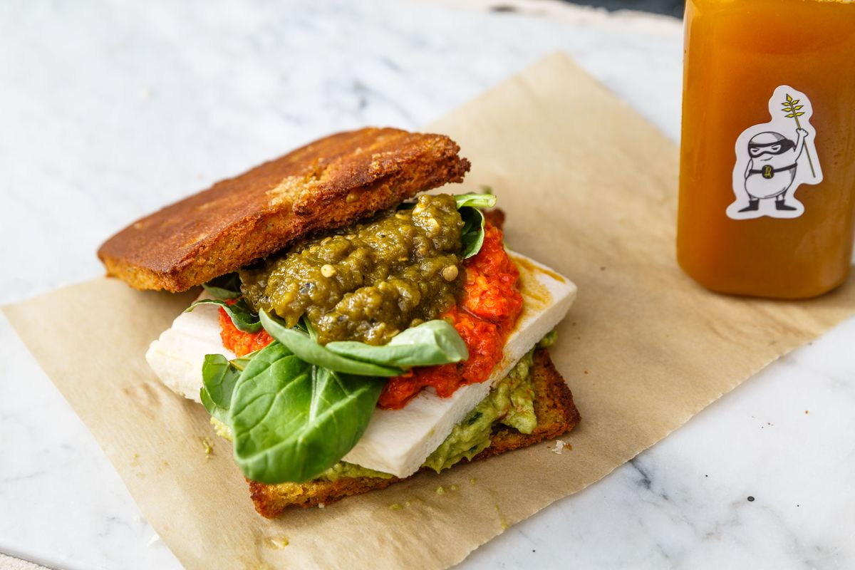 A sandwich topped with green and red sauces, spinach, and a slab of tofu rests on two thin slices of bread