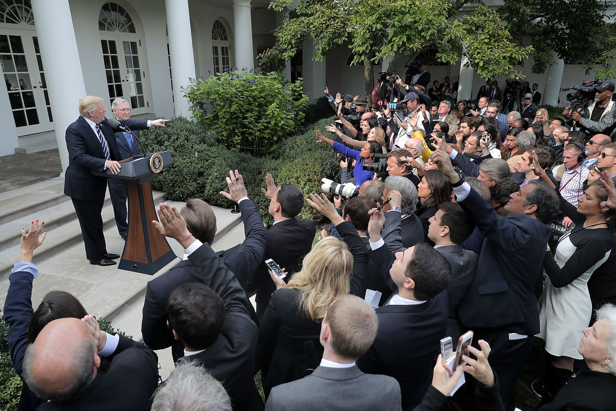 President Trump and Sen. Mitch McConnell speak to the press from behind a podium in the Rose Garden of the White House.