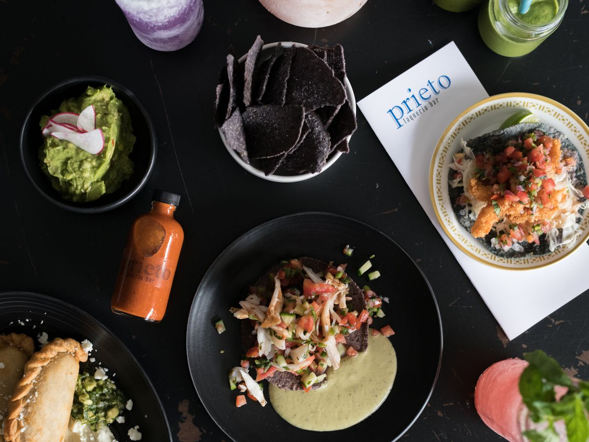 A spread of tacos, chips, salsa, and ceviche on a black table