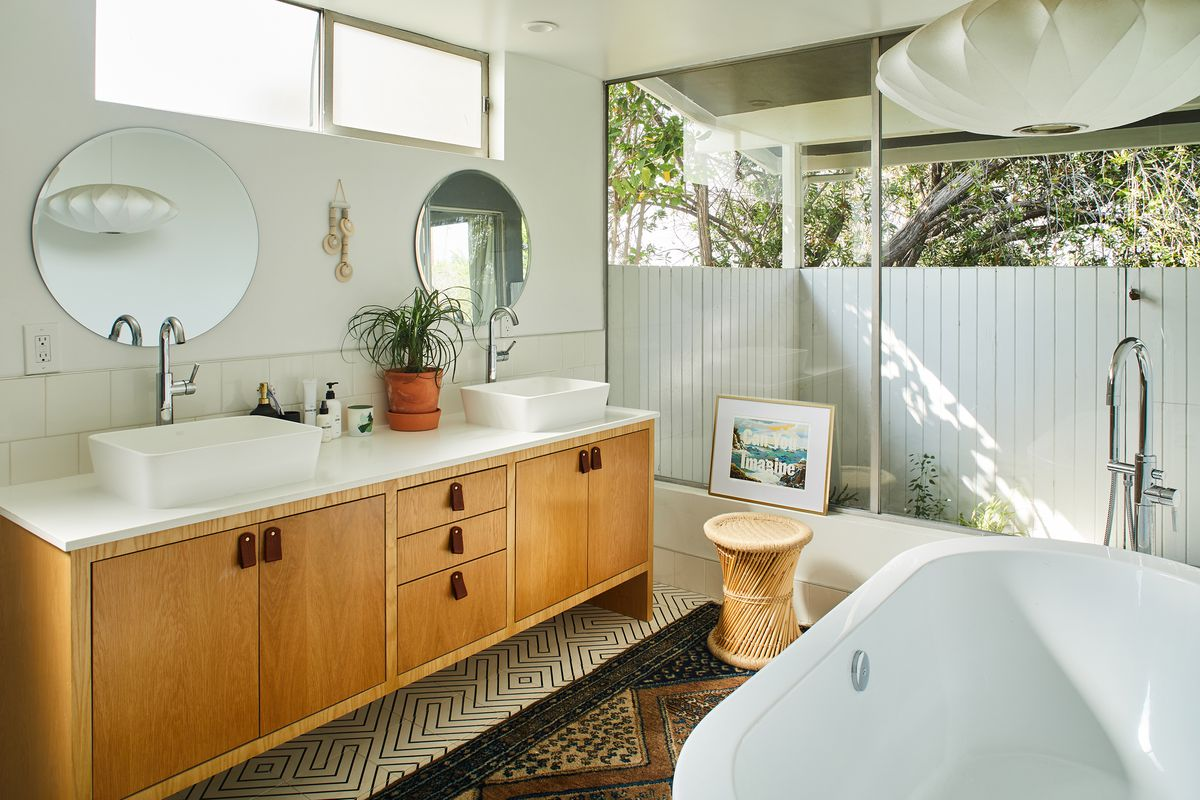 In this bathroom, there is a white bathtub, a wooden sink with white countertops, and two sinks. There are two mirrors hanging over the sink. There is a black and white patterned tile floor with a patterned area rug.