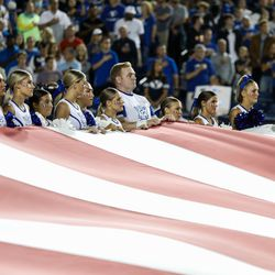 BYU cheerleaders hold the American flag as BYU and Utah compete in an NCAA college football gameat LaVell Edwards Stadium in Provo on Saturday, Sept. 11, 2021.