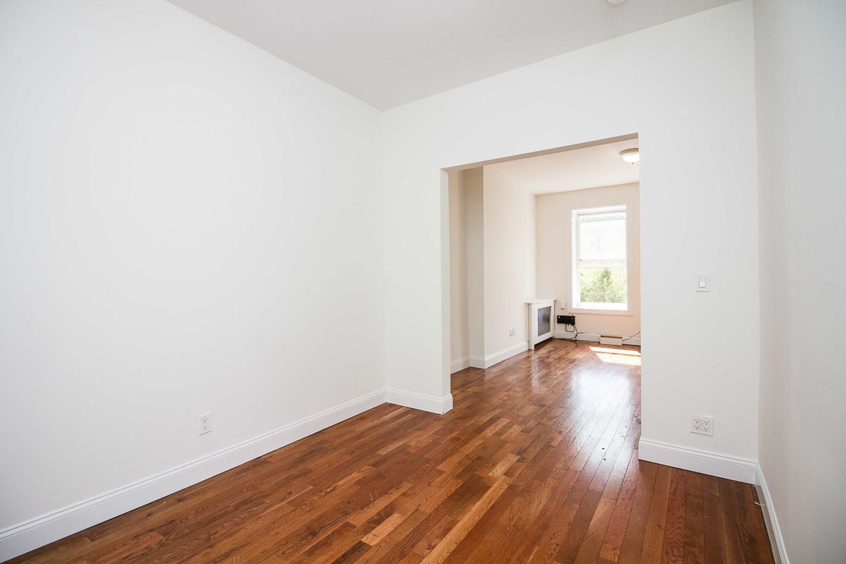 A living area with beige walls, base moldings, and hardwood floors.
