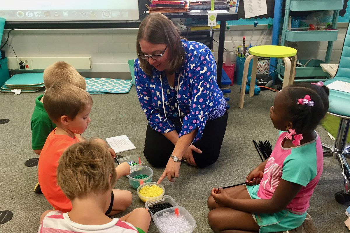 Kristin Poindexter helps her kindergarten students assemble butterfly bracelets in her science class at Spring Mill Elementary School in Washington Township.