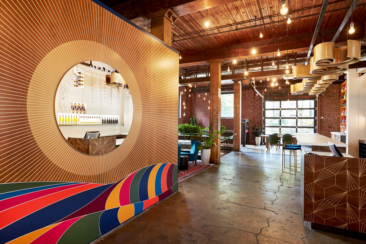 """At Erath's Peal District tasting room, a large wooden wall painted with colorful waves separates a small sitting area from the bar, where """"Dundee"""" is written in golden letters"""