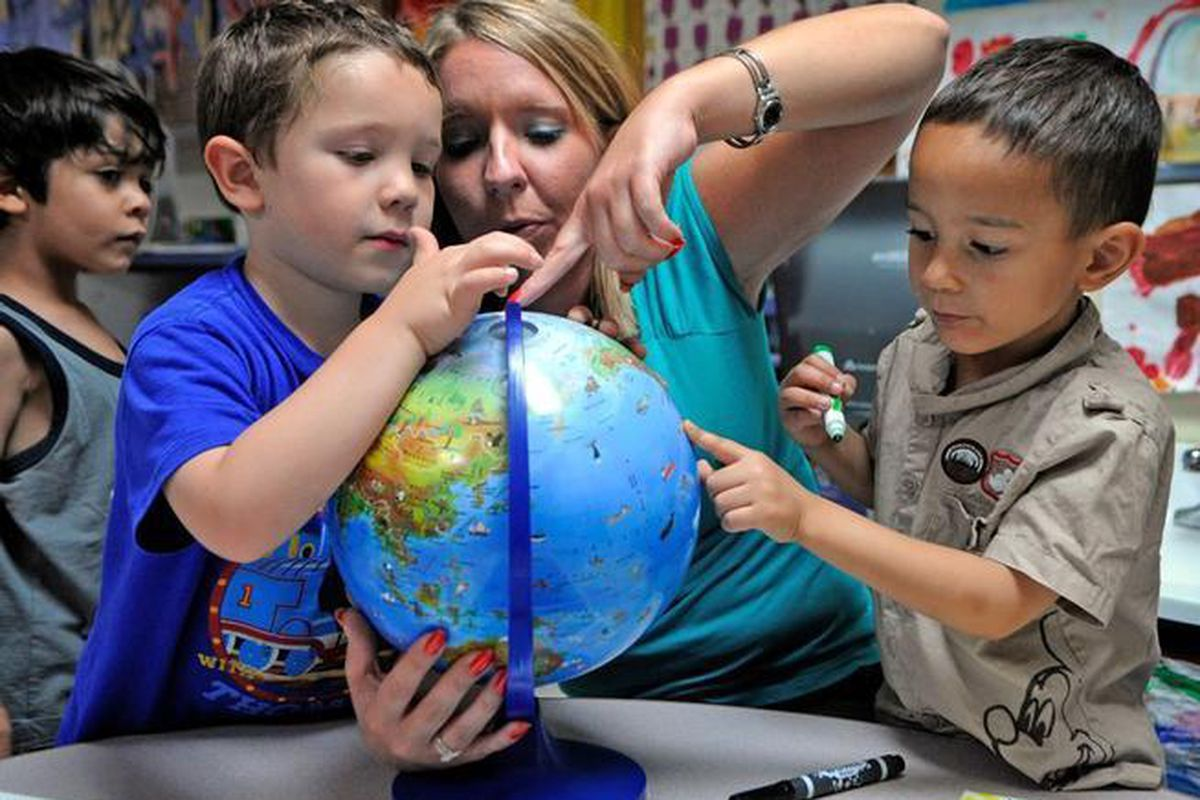 A woman and two young boys point to places on a globe.