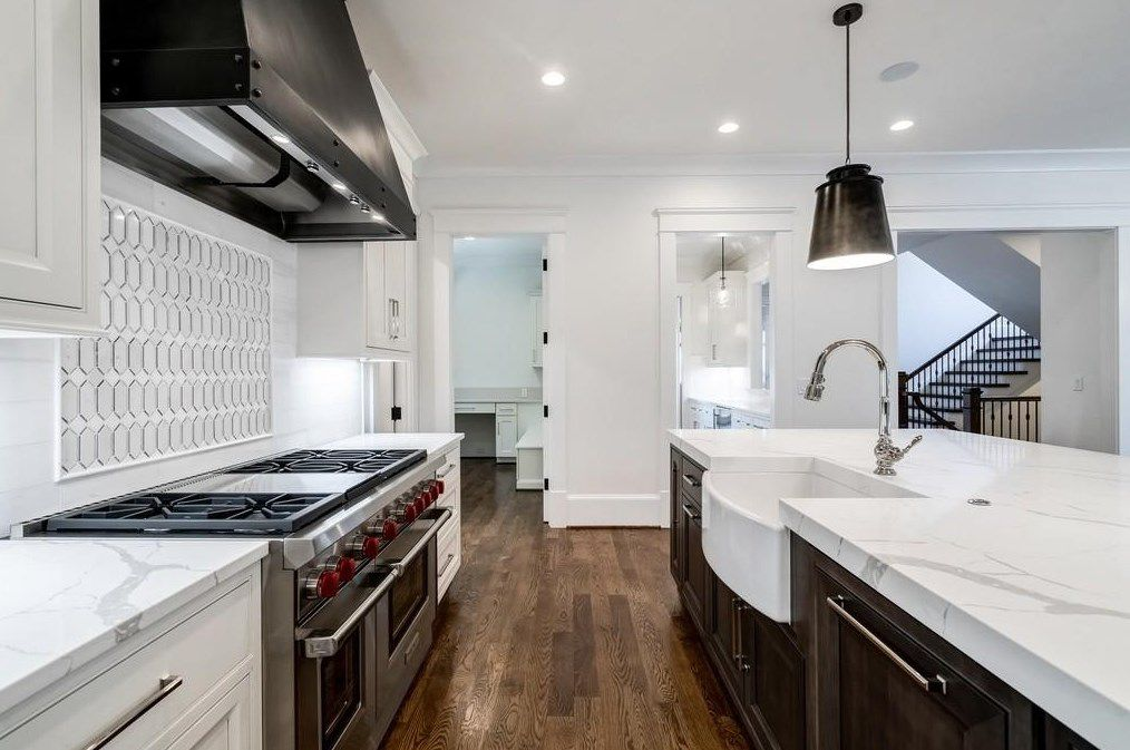 A white kitchen with a big range hood and pendants.