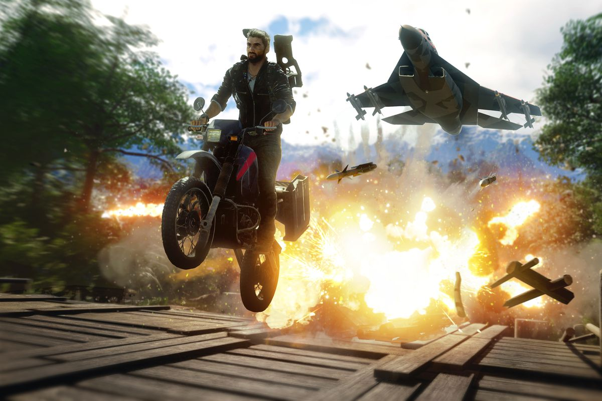 Just Cause 4 - Rico riding a motorcycle across a bridge away from an explosion while a fighter jet trails him overhead
