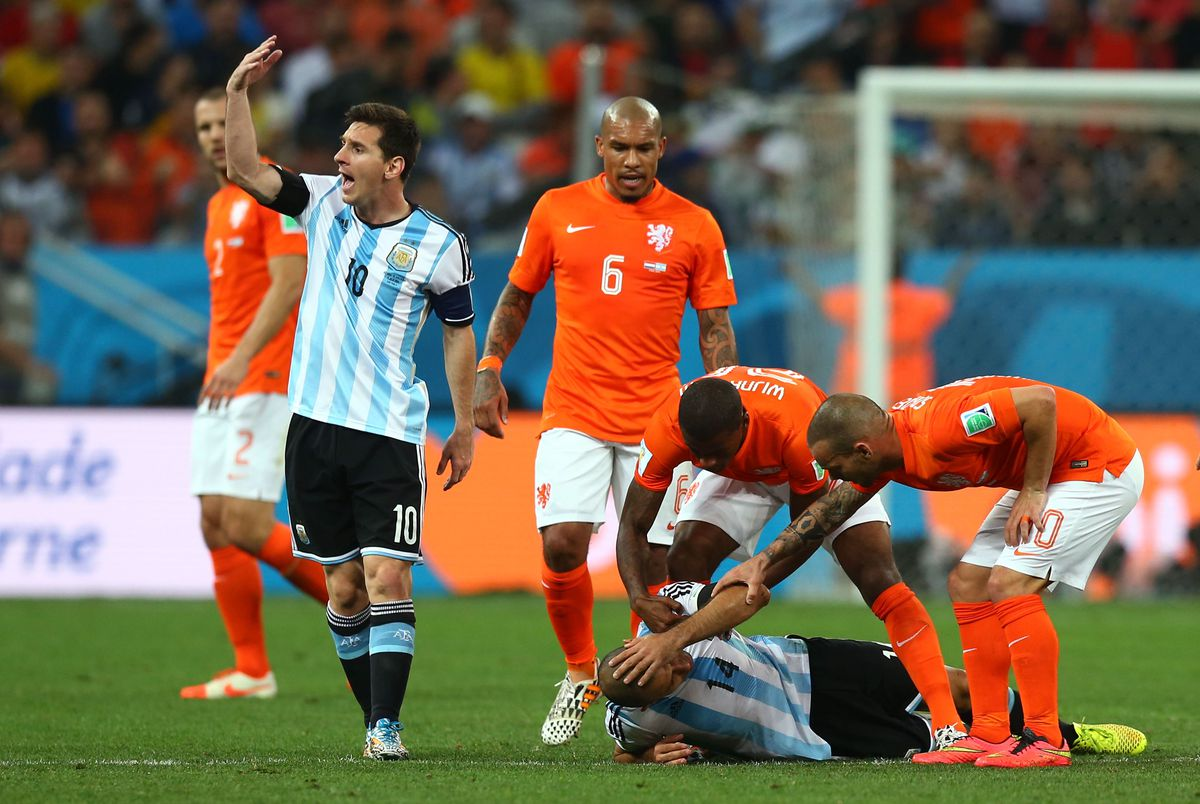 Lionel Messi requests treatment for Javier Mascherano during a 2014 World Cup match against the Netherlands (GettyImages)