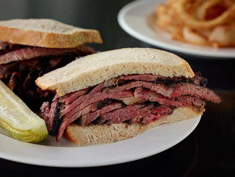 a pastrami sandwich on untoasted rye bread with a pickle