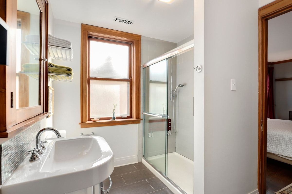 A bright bathroom with a freestanding sink, glass shower, and gray tile flooring. There's a single window and a bed can be seen in the next room.