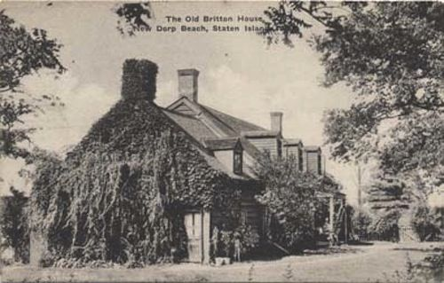 A historic image of the exterior of a house. The house is made of stone and there are plants and greenery growing along one side of the house. The house is surrounded by trees.