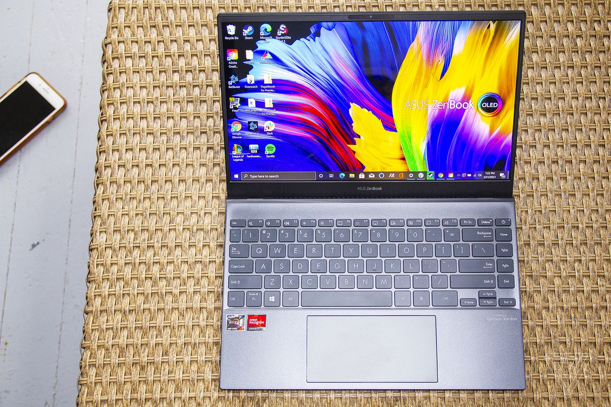 The Asus Zenbook 13 OELD seen from above. The screen displays Zenbook and OLED logos on a multicolor background.
