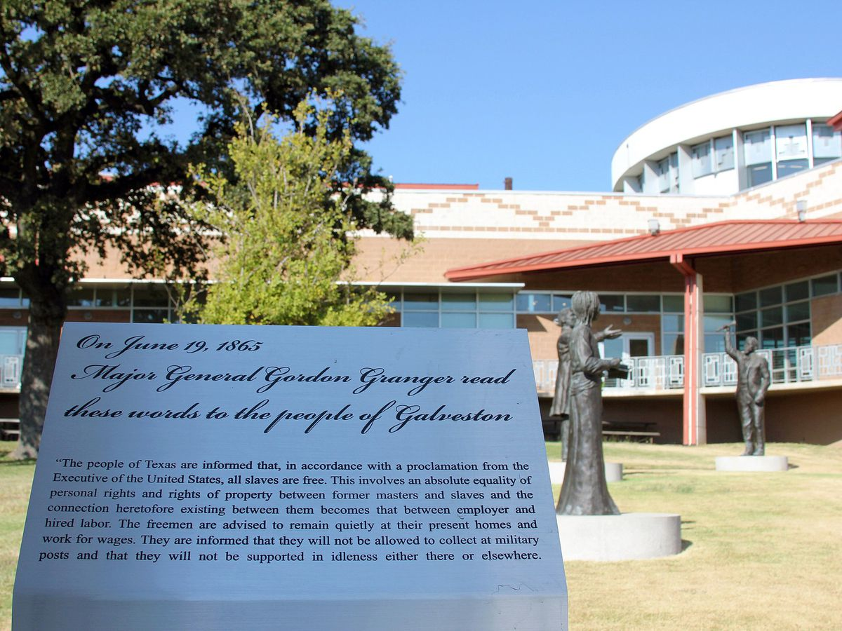 A plaque with Juneteenth proclamation in front of rounded museum building