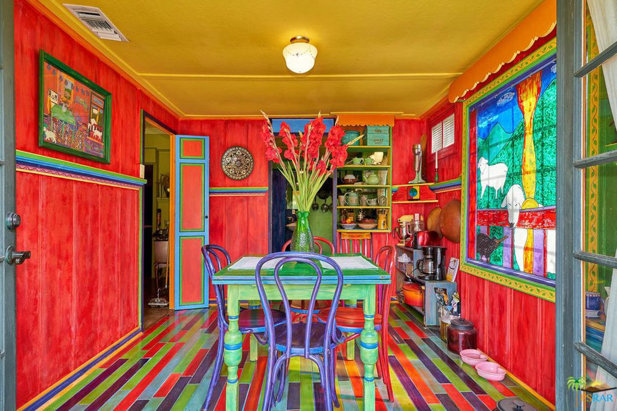 Interior shot of a dining room red walls, yellow ceilings, multi-colored hardwood floors, rainbow trimming, and a painted dining set.