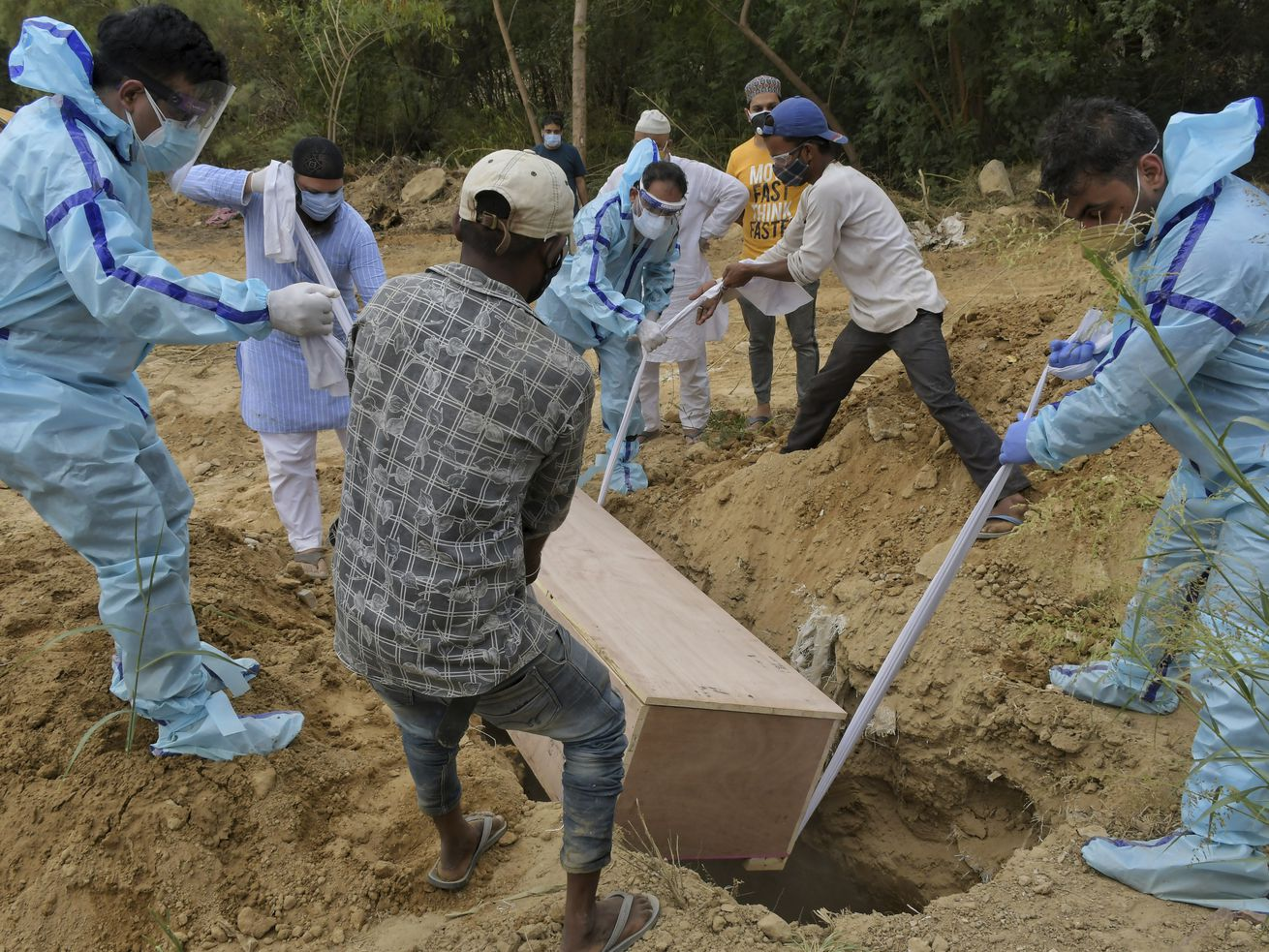 Relatives bury the body of a COVID-19 victim at a graveyard in New Delhi, India, Tuesday, May 4, 2021.