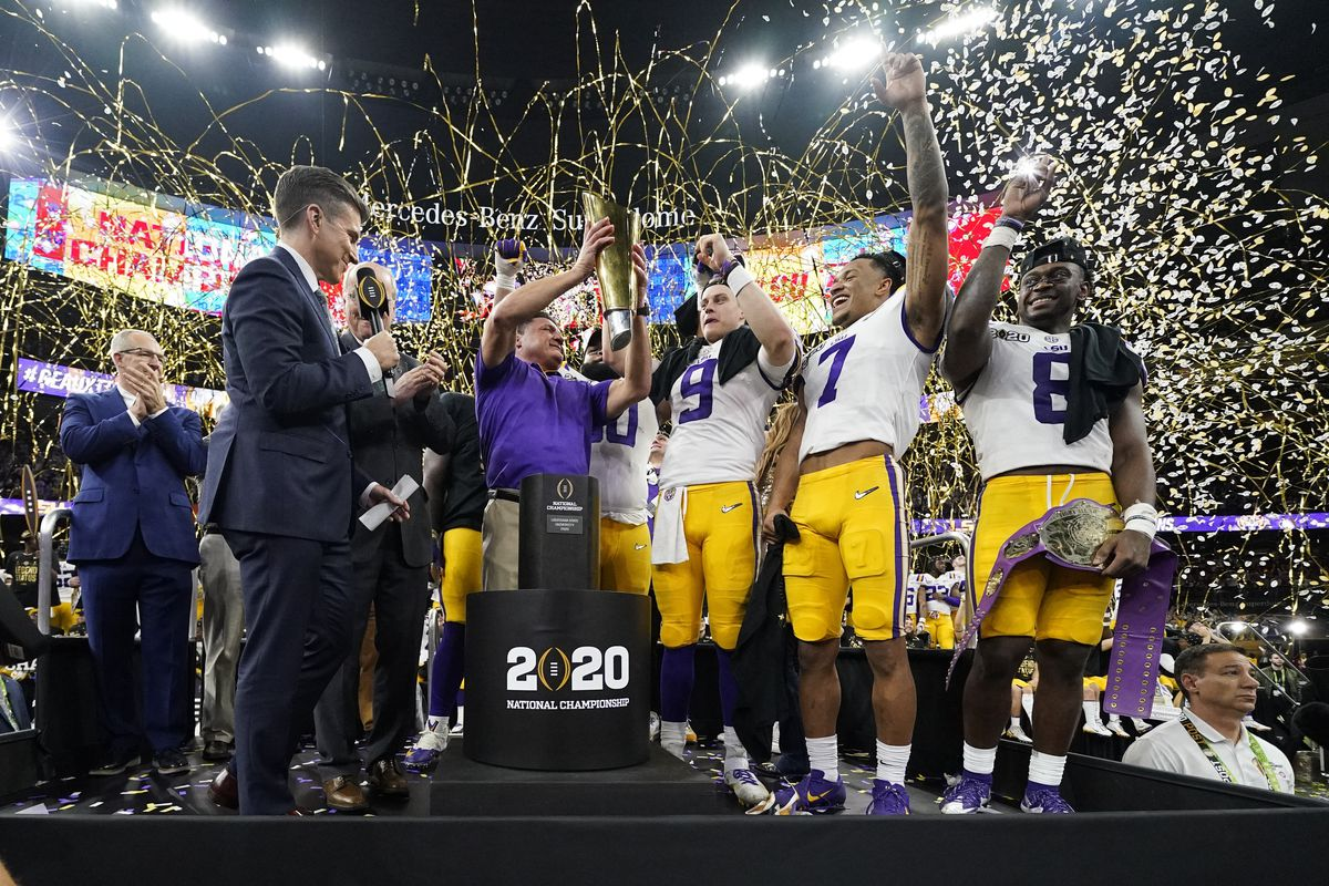 In this Jan. 13, 2020, file photo, LSU head coach Ed Orgeron holds the trophy after his team beat Clemson in the NCAA college football championship. Dozens of LSU players are now in quarantine because of COVID-19.