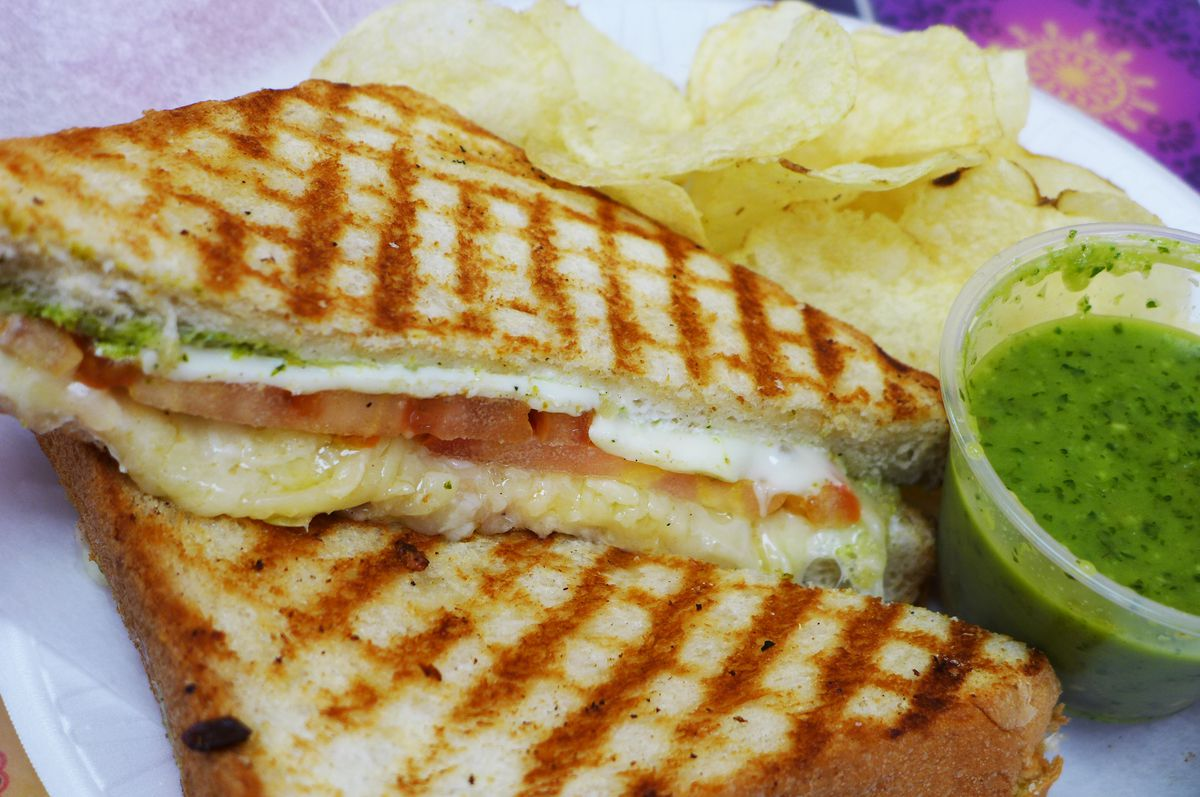 A toasted cheese sandwich with tomato in the middle and green chutney on the side.