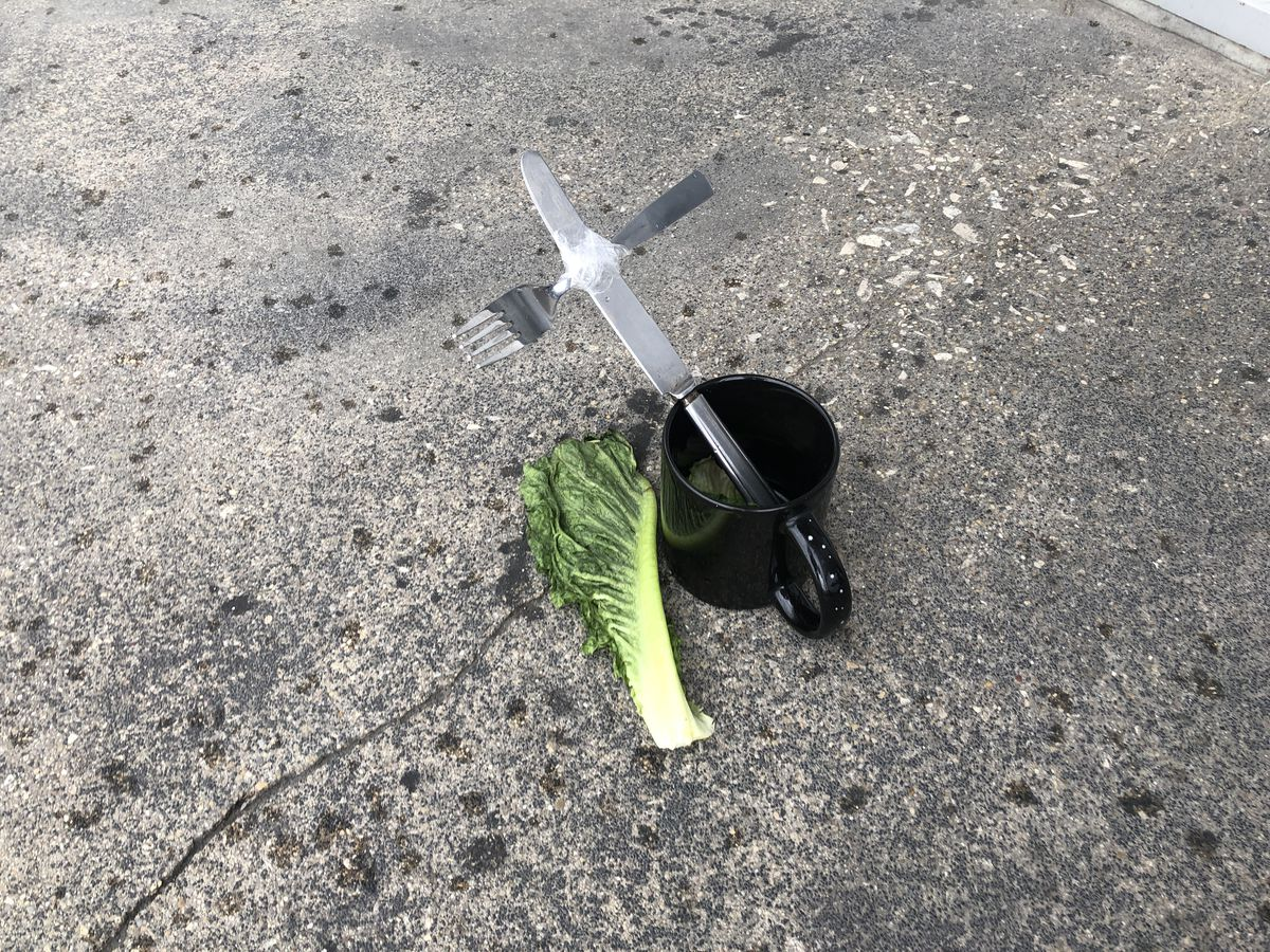 A black coffee mug holds a metal knife and fork taped together to form a cross. A piece of lettuce sits nest to the mug on a sidewalk.