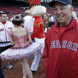Boston Red Sox manager Bobby Valentine, right, talks with fans as a Nutcracker ballerina and soldier walk along the first base line prior to a baseball game against the Baltimore Orioles at Fenway Park in Boston, Friday, Sept. 21, 2012.