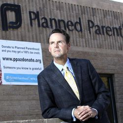In this photo taken Sunday, Jan. 23, 2011, Bryan Howard, President and CEO of Planned Parenthood Arizona, Inc., poses in front of a Planned Parenthood facility in Tucson, Ariz.  Planned Parenthood, a perennial protest target because of its role in providing abortions, has notified the FBI that at least 12 of its health centers were visited recently by a man purporting to be a sex trafficker but who may instead be part of an attempted ruse to entrap clinic employees.
