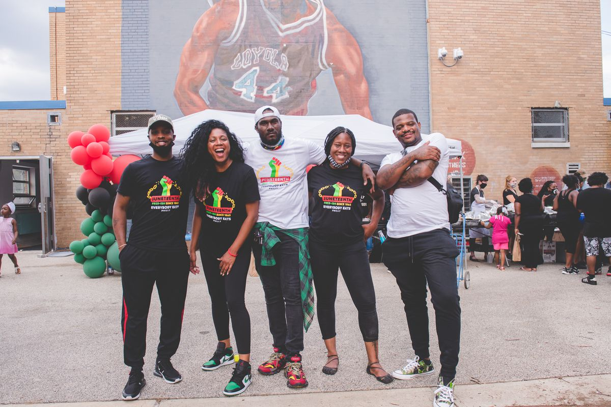 five people standing facing camera with mural of a basketball playing behind them