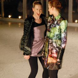 A figure skater skates up and surprises one of the still models.