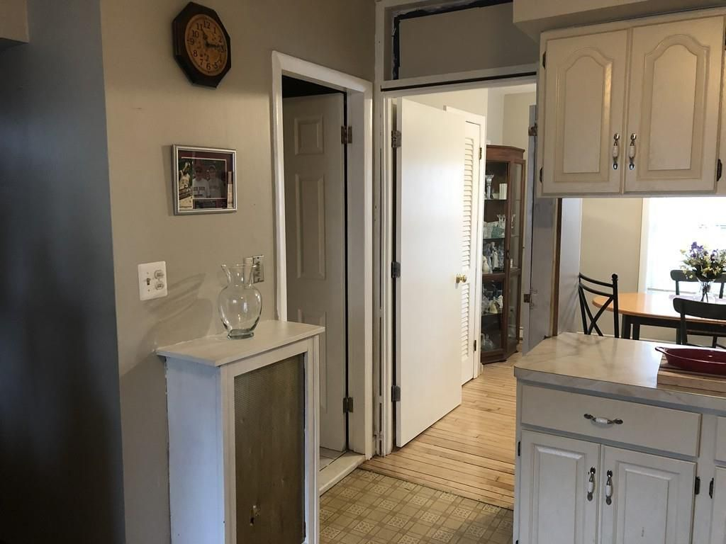 The end of a kitchen counter, with an open door leading to a bathroom and another leading to a living room.