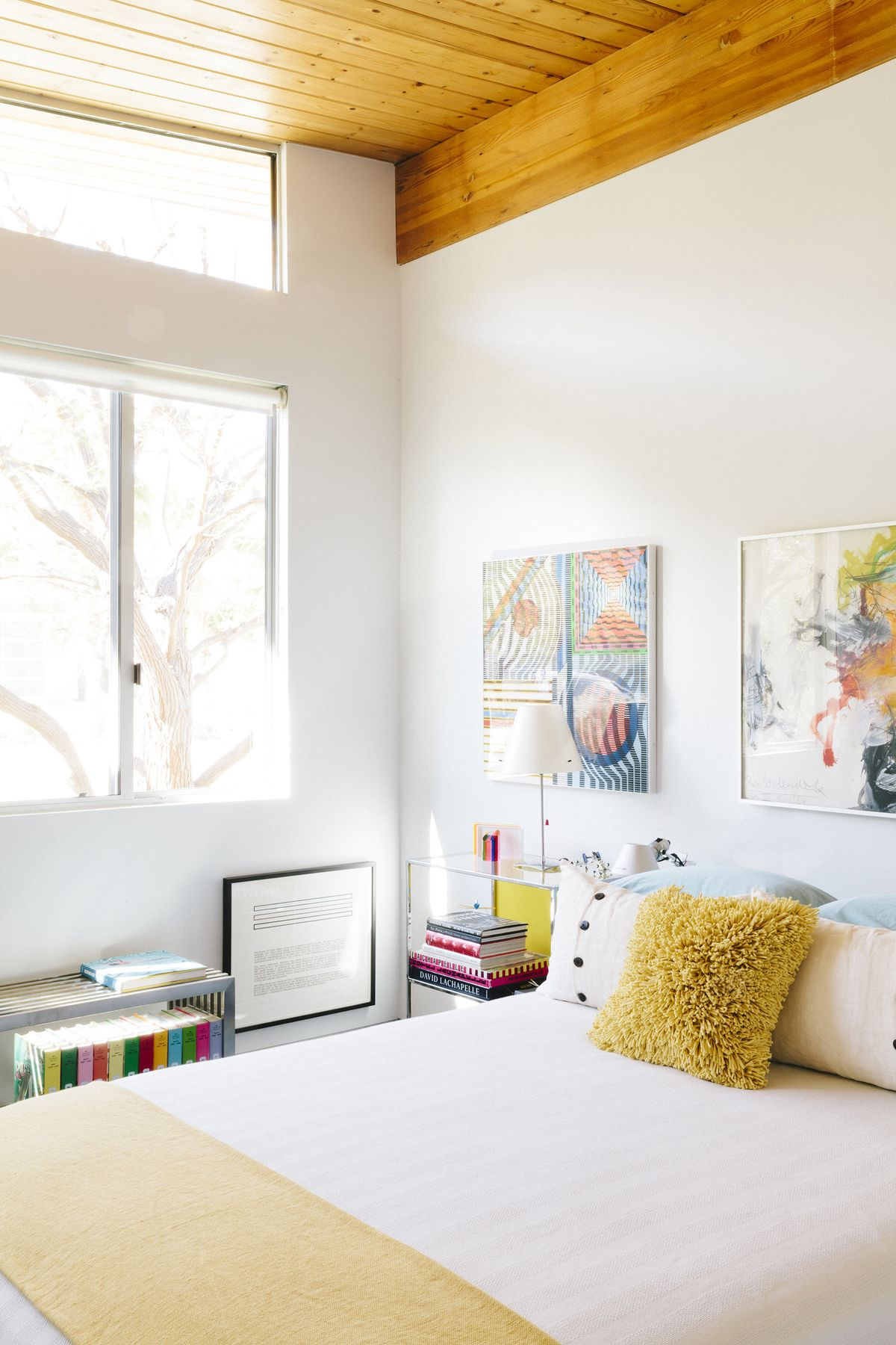 A bedroom. There is a large bed with white bed linens, a yellow blanket, and multiple assorted pillows. There is colorful artwork hanging above the bed. There is a large window letting in natural light.