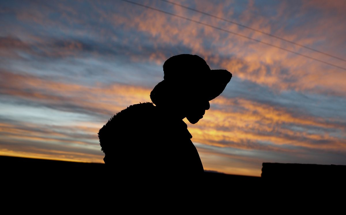 """Mayor Rufino Choque is silhouetted against a sunset sky in the Urus del Lago Poopo Indigenous community in Punaca, Bolivia. """"Our grandfathers thought the lake would last all their lives,"""" he says."""
