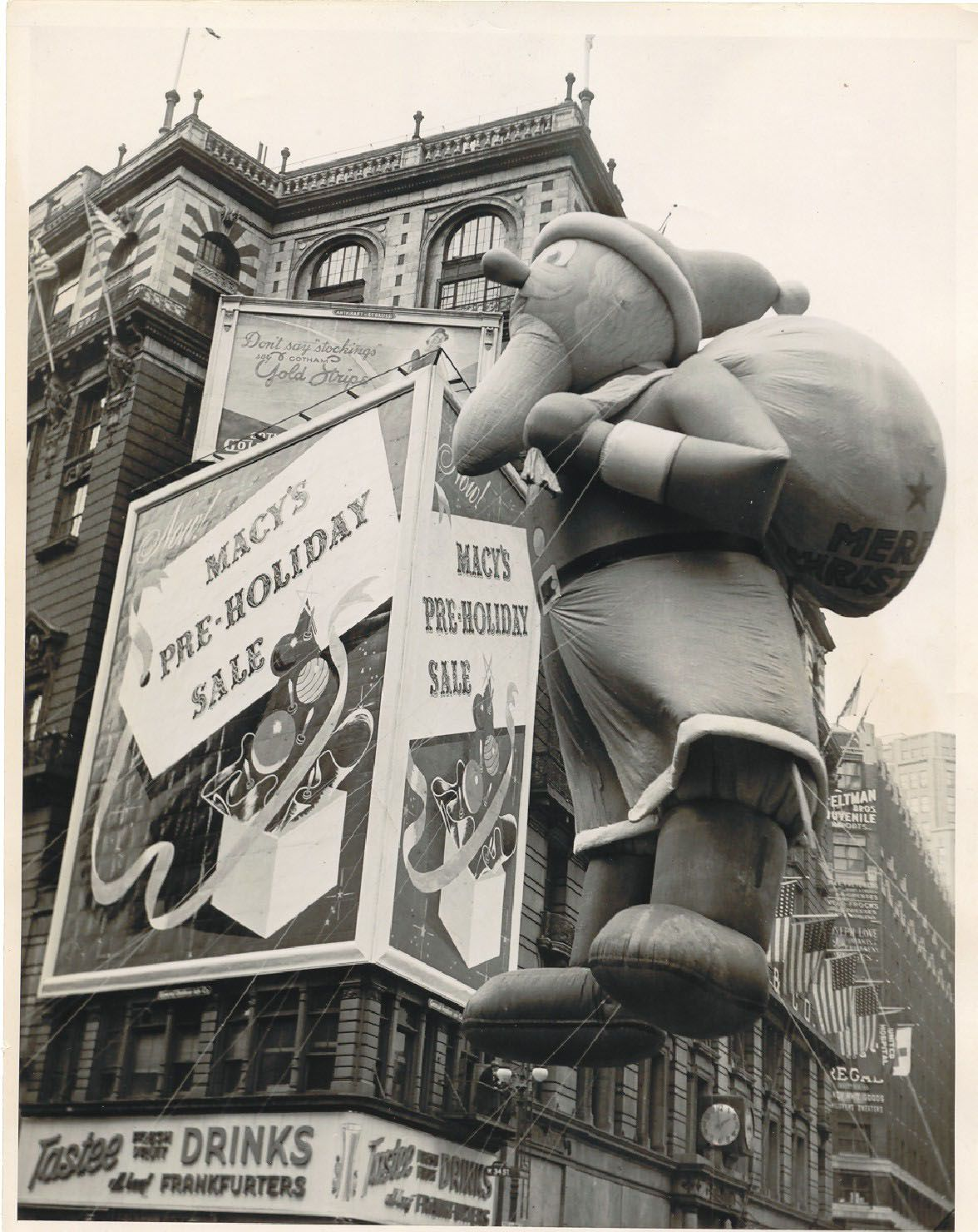 A santa balloon floats by Macy's in new York City in a black and white 1940 photo
