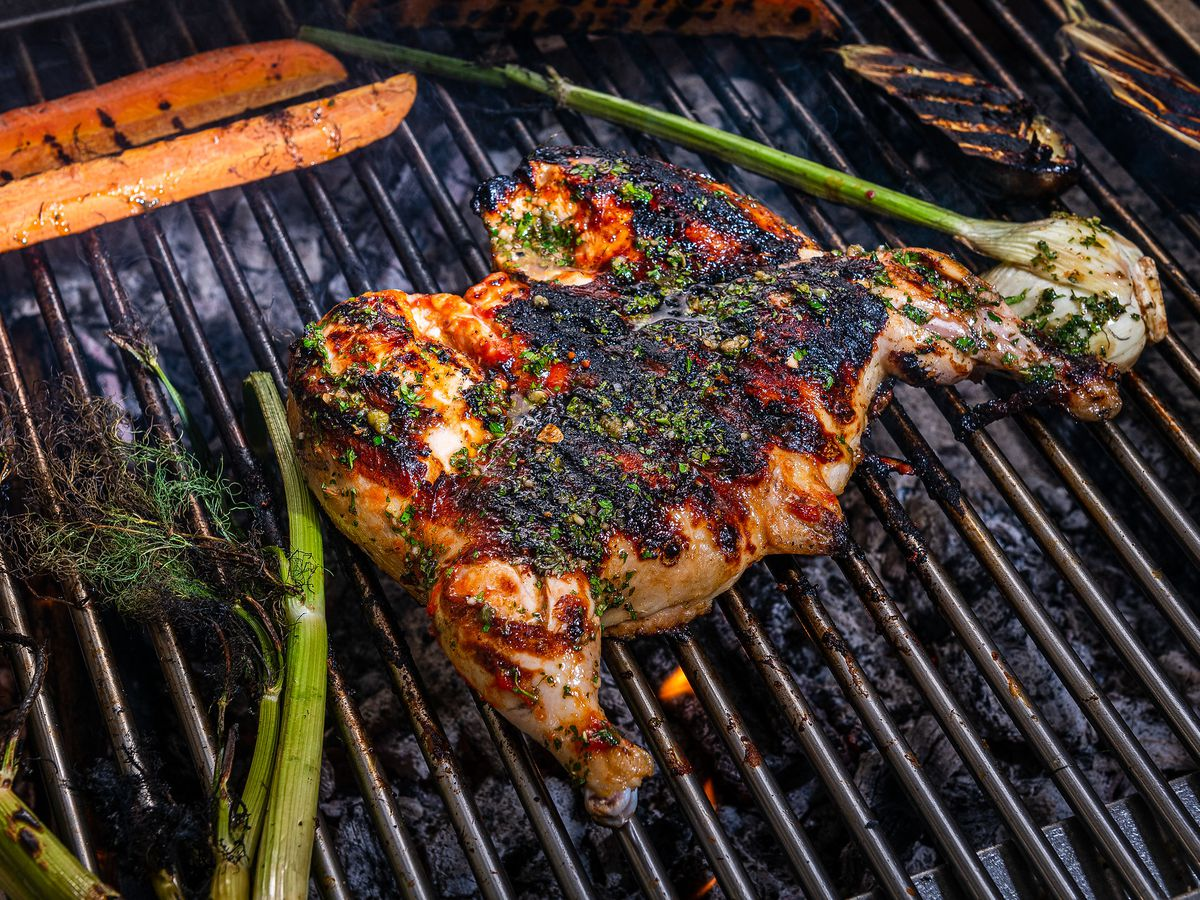 A charred, split chicken cooks on a wood-fired grill at L'Ardente.