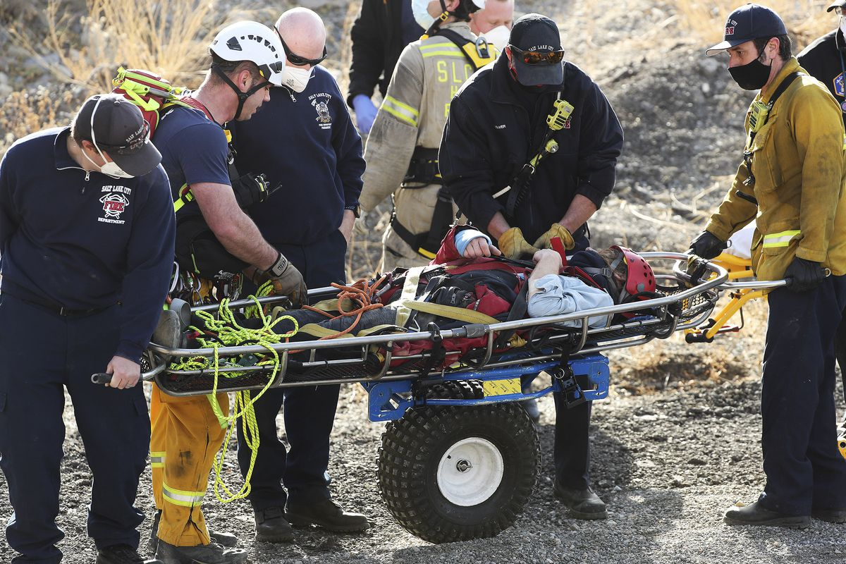 Salt Lake City Fire Department first-responders aid a 29-year-old man who fell from a cliff in the gravel pit on Victory Road in Salt Lake City on Sunday, Dec. 27, 2020. The injured man was stuck on a ledge for more than five hours, firefighters reported.