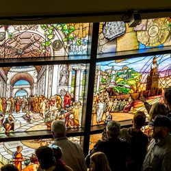 """The crowd gets a close look at the stained glass after the unveiling of the """"Roots of Knowledge"""" in the Fulton Library on the Utah Valley University campus in Orem on Friday, Nov. 18, 2016."""