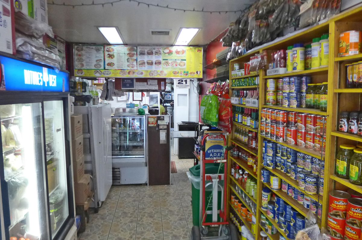 A narrow store with groceries on shelves on either side.