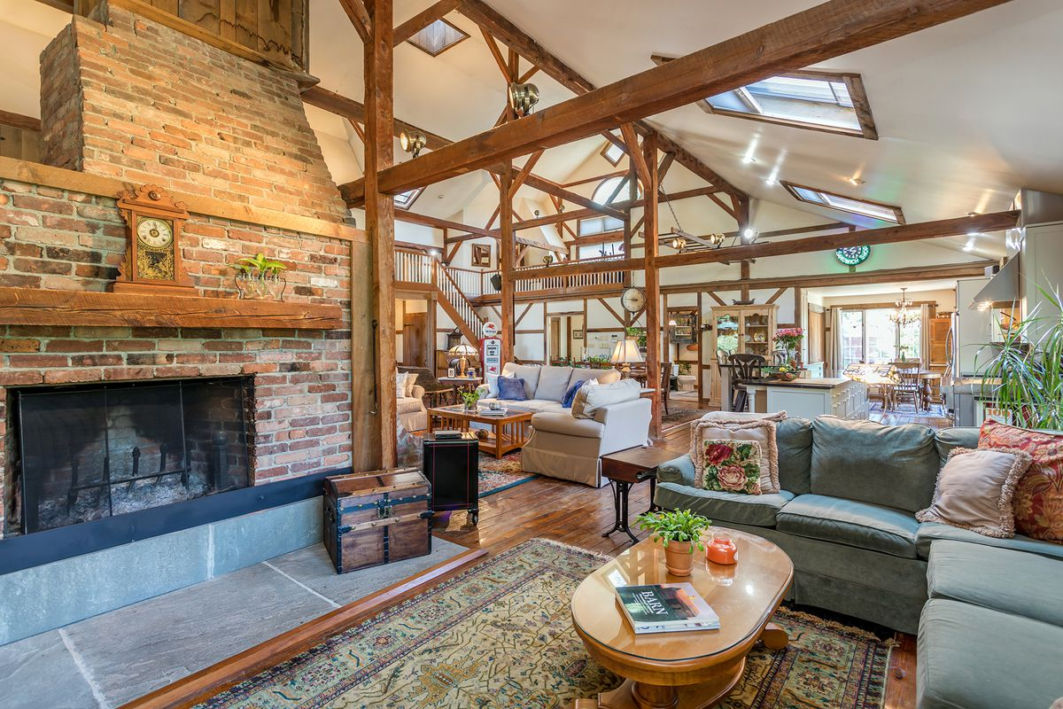 The interior of a barn conversion into a house features an open floor plan with brick fireplaces and couches.