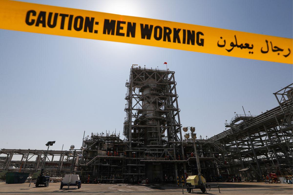 "Saudi Arabaian oil factory with yellow tape reading ""Caution: Men Working"""