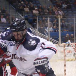 UConn's Jesse Schwartz (17) battles for the puck with Northeastern's Jarrett Fennell (61).