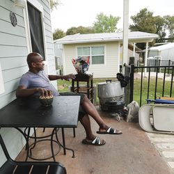 Bryan Coward sits on the porch of his tiny home at Community First! Village in Austin, Texas, on Tuesday, Oct. 20, 2020.