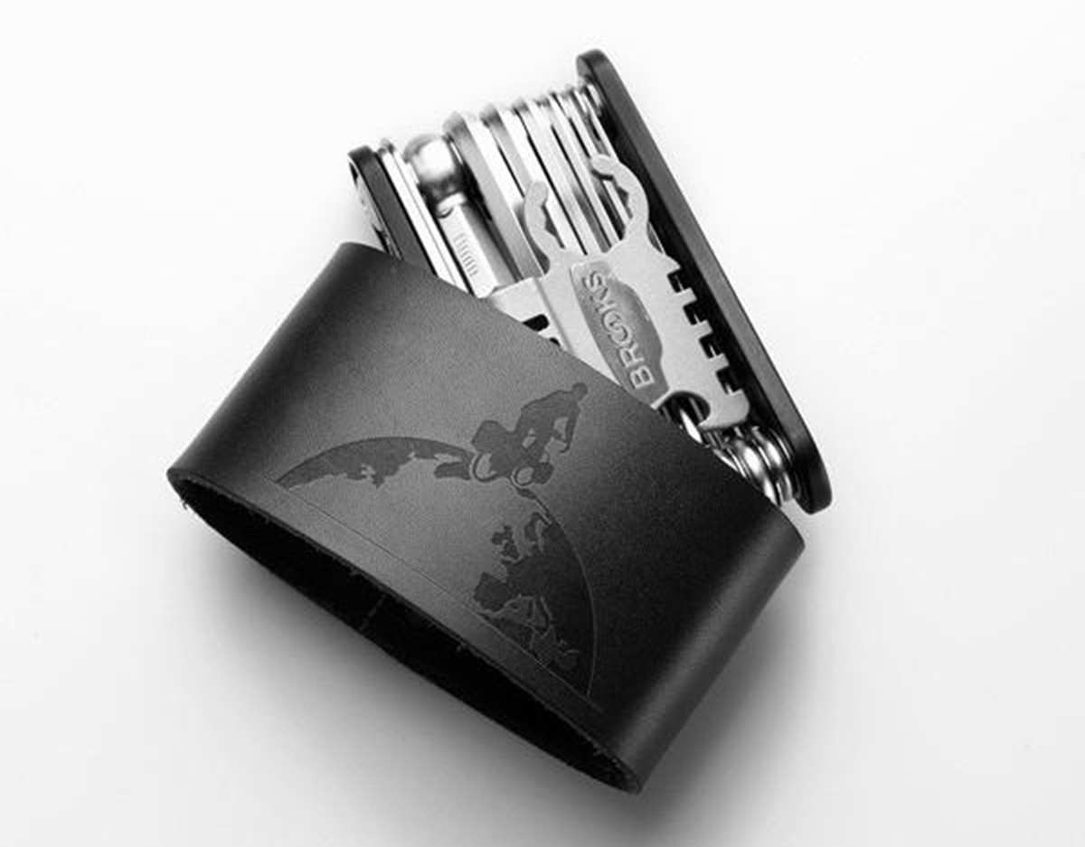 A portable tool set with a black leather sleeve.
