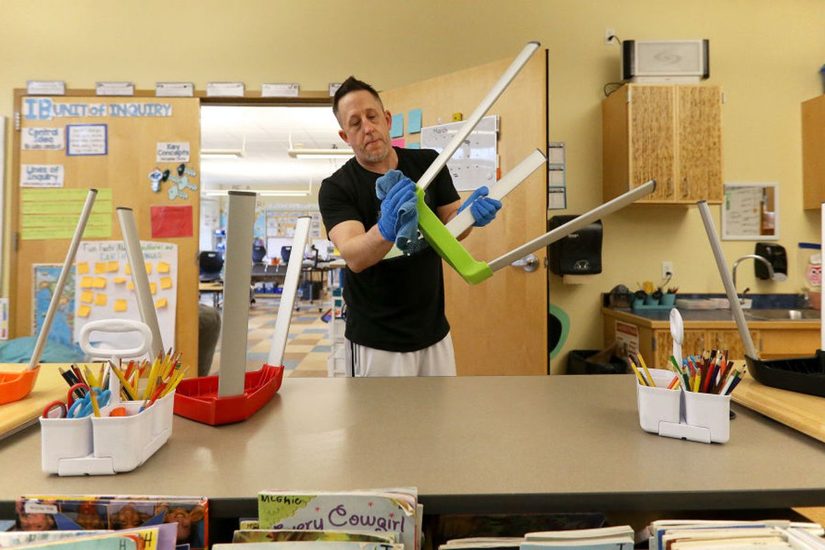 """PORTLAND, ME - MARCH 6: Joseph Miller, a custodian at Ocean Avenue Elementary School, uses a disinfectant-soaked towel to clean a chair and other """"touch areas"""" throughout a classroom. (Staff photo by Ben McCanna/Portland Press Herald via Getty Images)"""