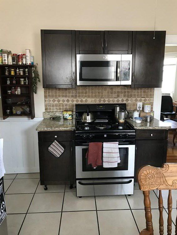 Part of a kitchen with a small counter and a mounted microwave.