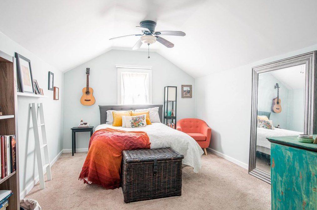 A white bedroom with orange chairs and orange bedspread.