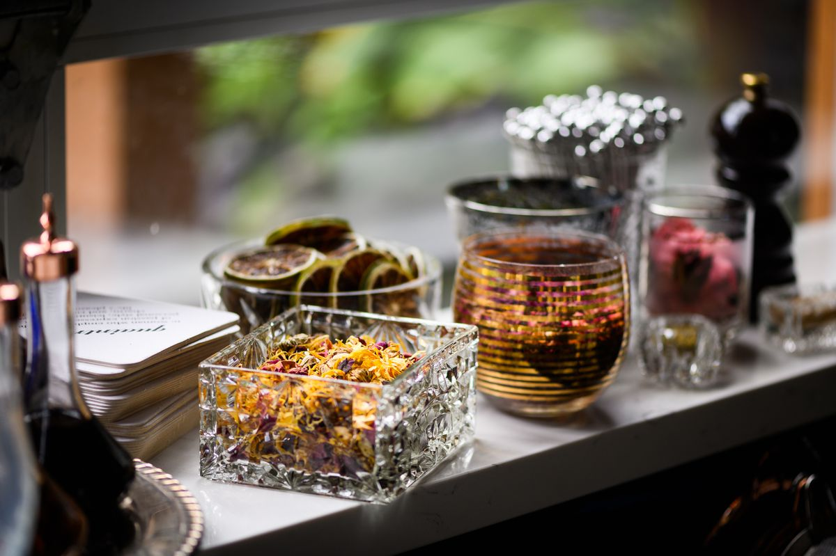 On a window ledge, glass containers hold a variety of cocktail garnishes including dehydrated lime wheels and dried flower.