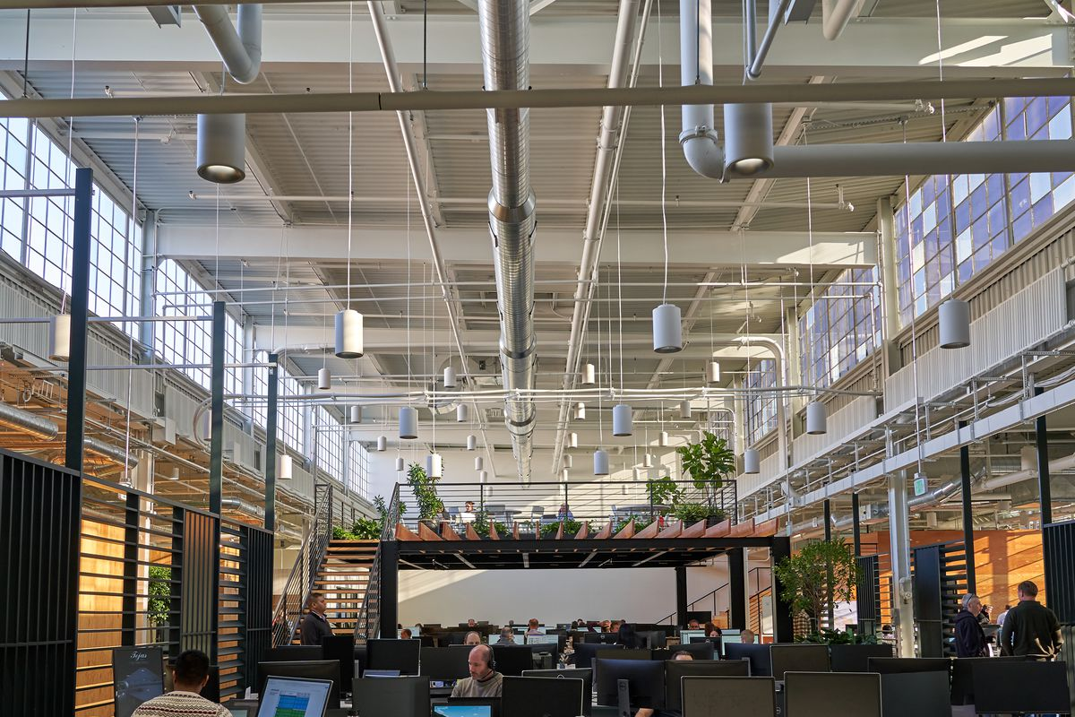 Employees sit at long desks in an industrial space with high ceilings.