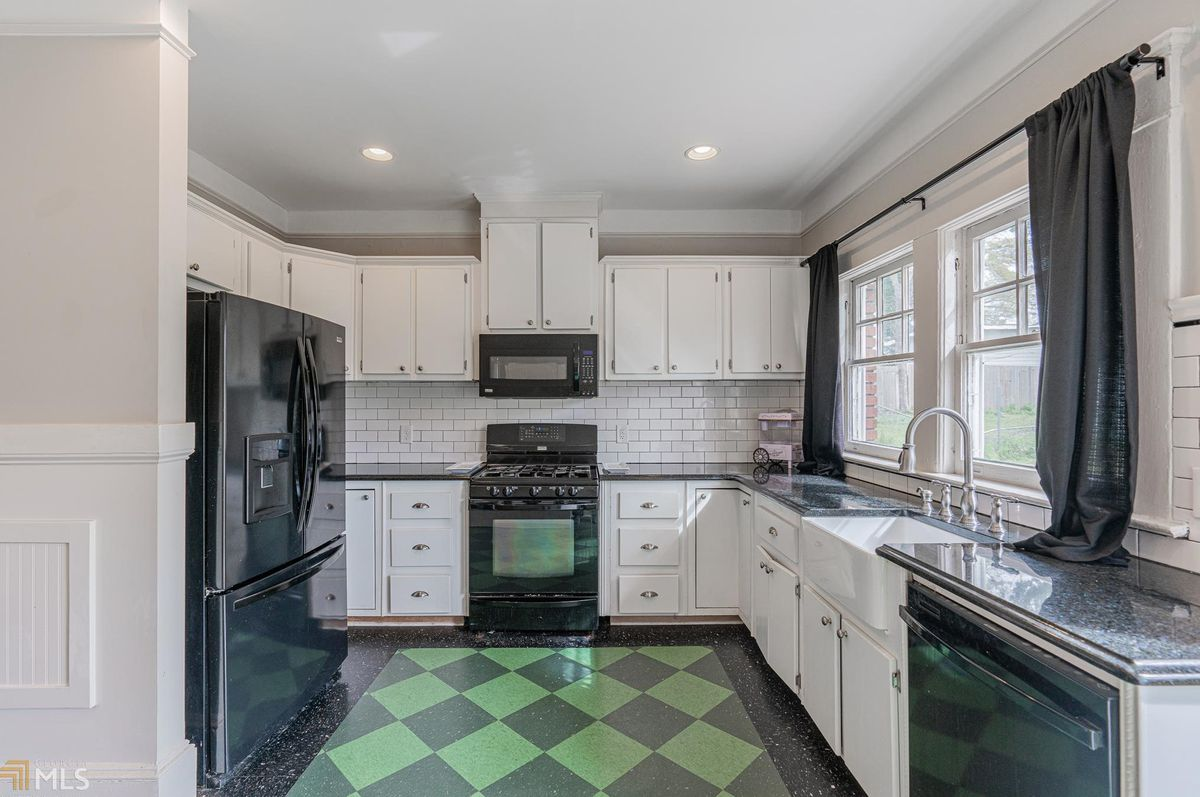 A white and black kitchen with green and gray tiles on the floor.