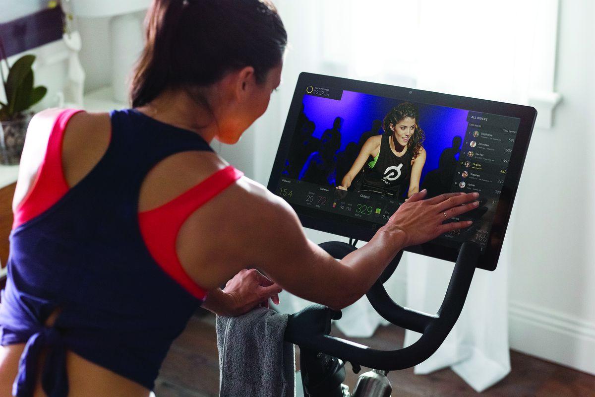 A woman watching a workout video while riding a Peloton bike.