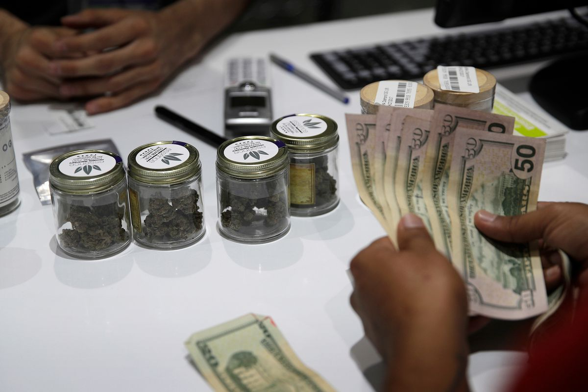 FILE - In this July 1, 2017, file photo, a person buys marijuana at the Essence cannabis dispensary in Las Vegas. (AP Photo/John Locher, File) ORG XMIT: LA538