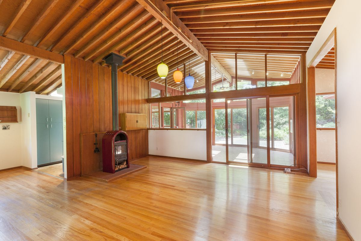 Interior photo of vaulted great room with old-fashioned furnace look out toward the yard through a glazed sunroom.