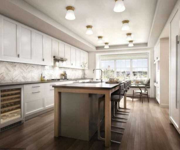 A kitchen area with an island, chairs, white cabinetry, and hardwood floors.