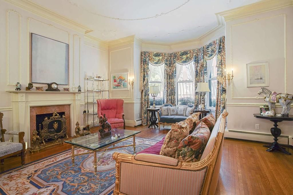A posh living room with a bay window, a couch, a coffee table, and they're both facing the fireplace.